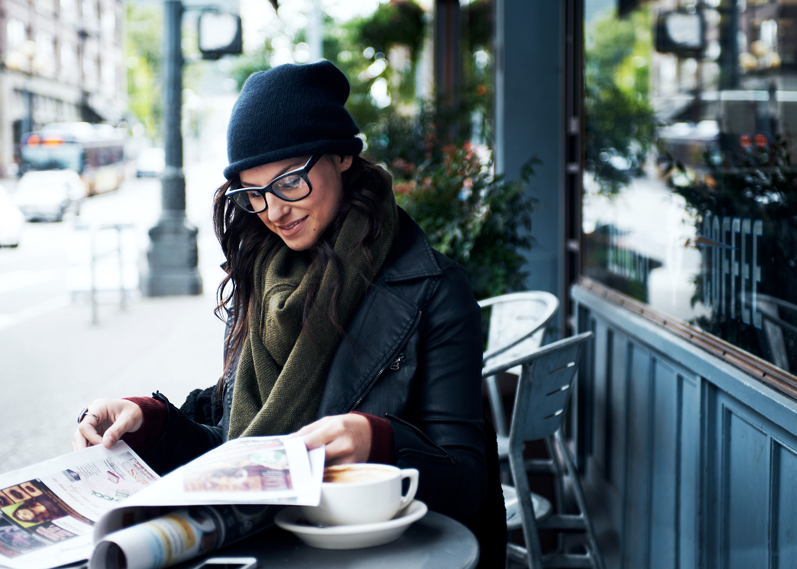 girl sits with coffee and paper in this seattle  lifestyle photoshoot
