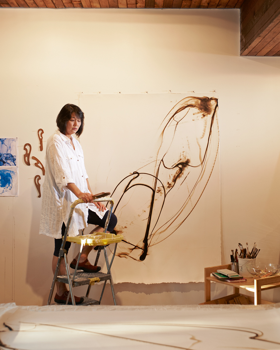 Artist, EtsukoIchikawa works on her latest work as Amos Morgan takes her portrait