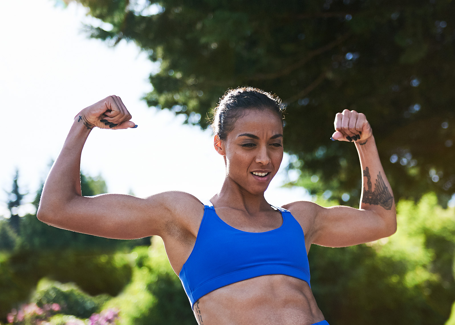 woman athlete flexes her muscles