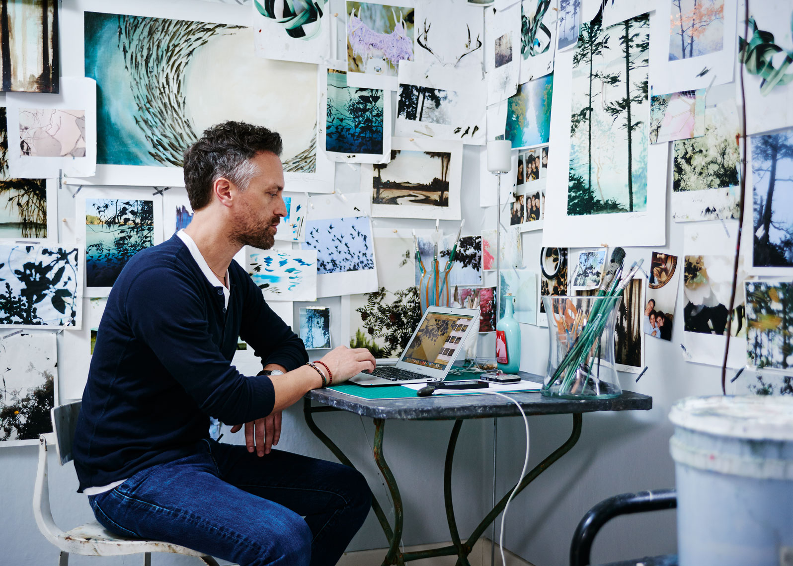 Artist Jared Rue sits at his desk